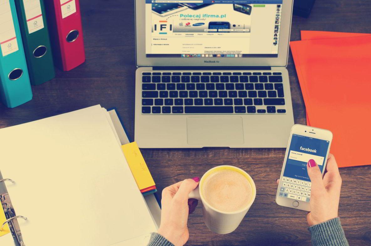 vrouw zit aan haar bureau met iphone, macbook en kopje koffie
